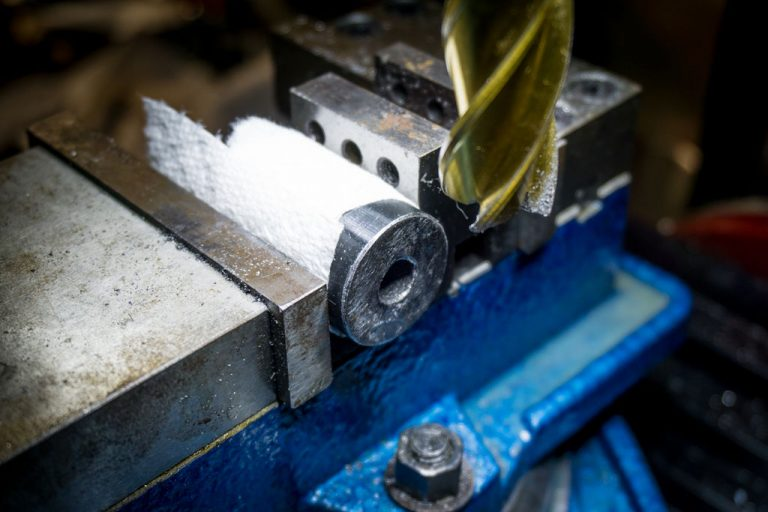 A milling machine is the ideal tool for this project. Or a lathe if you feel like showing off... But if you don't, a hand saw and a bench grinder would probably do the trick.