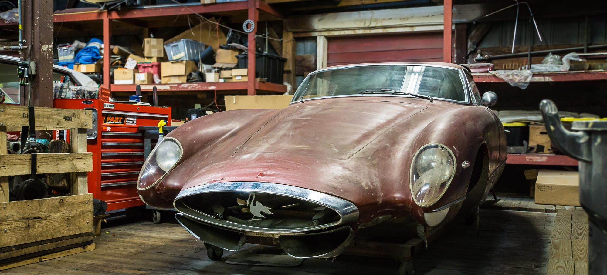 Vintage car in cluttered workshop-garage.